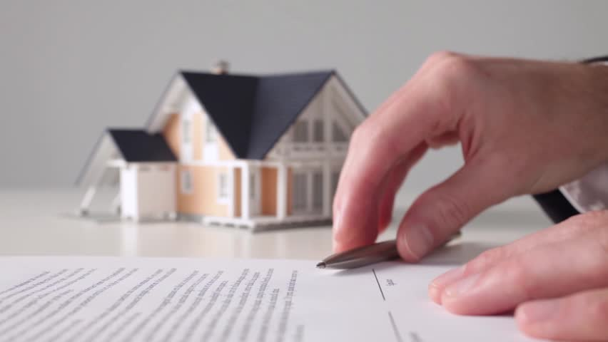 Mortgage contract sign. Model of the house and man confirming mortgage contract.