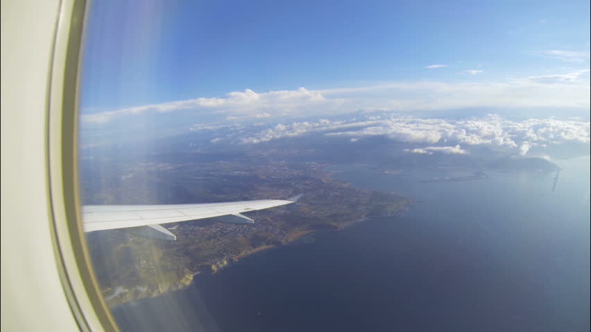 Wing of plane flying high over sea and seashore, sparse white clouds in distance #29804926
