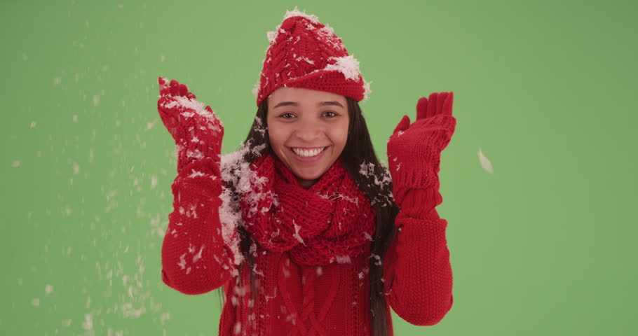 Laughing clapping Latina girl in a red sweater with snow falling on her on green screen. On green screen to be keyed or composited.