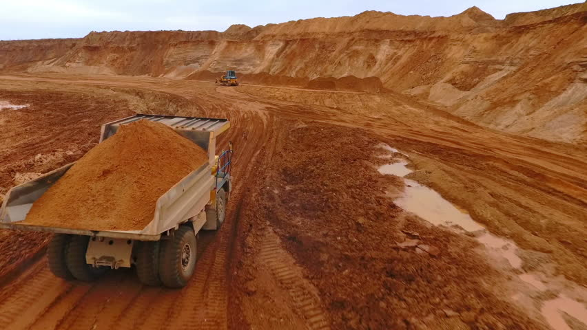 Mining truck transporting sand at sand quarry. Aerial view of mining machinery moving at sand mine. Sand work in mining industry