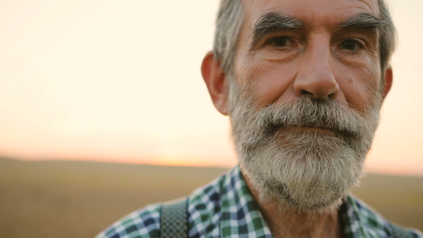 Close up portrait of senior smile man with beard looking to the camera in the golden field on the blue sky background sunny day .Face Happy Farmer Worker summer nature Farming Real people Concept