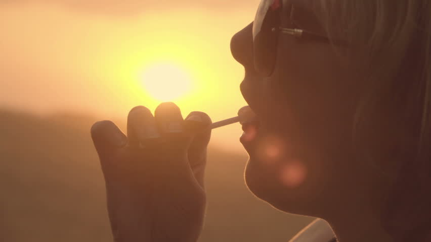 Girl eating lollipop, close-up face at sunset. Slow motion    Shutterstock HD Video #29824903