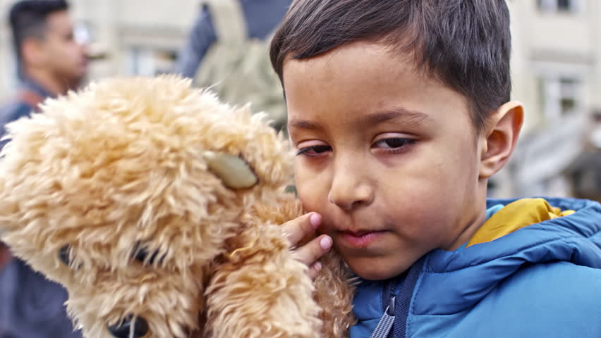 PAN with close up of sad Arab refugee boy with dirt on his face wearing puffy vest and holding plush bear