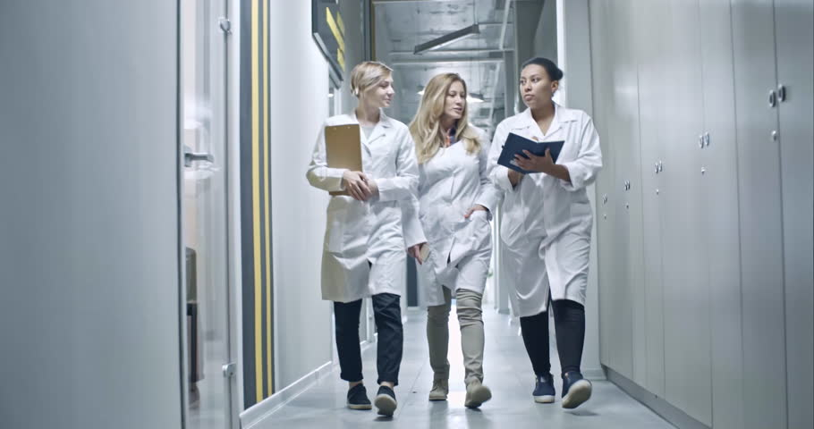 Three female factory engineers in lab coats walking through corridor towards camera and discussing information in organizer
