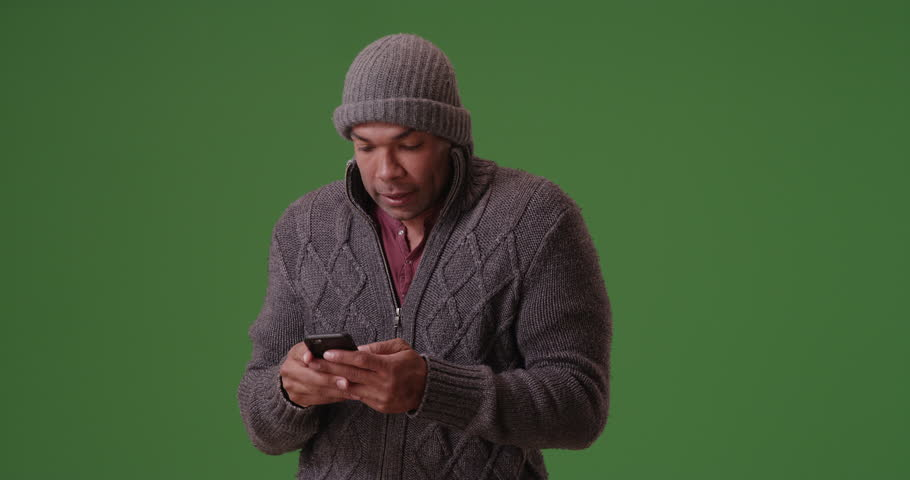 An African American man stands trembling on his smart phone on green screen. On green screen to be keyed or composited.