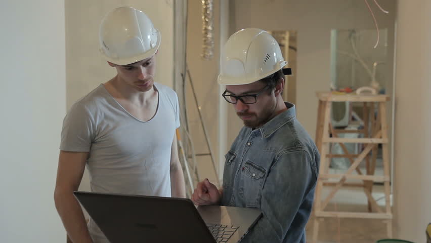 Architectures following drawings on laptop in building apartment in new house, check parameters according to images. Man boss looking on architectural design of building, compares, shows colleagues | Shutterstock HD Video #29856070