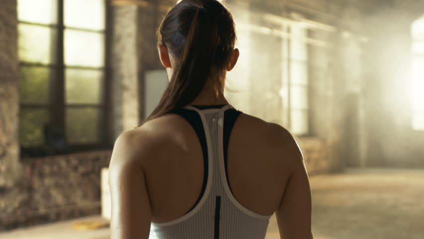 Follow-up Shot of Athletic Beautiful Woman Entering Gym in Slow Motion. She's Confident, Building is Industrial and Hardcore, Various Cross fitness/ Bodybuilding Equipment lying on the Floor. 4K UHD.