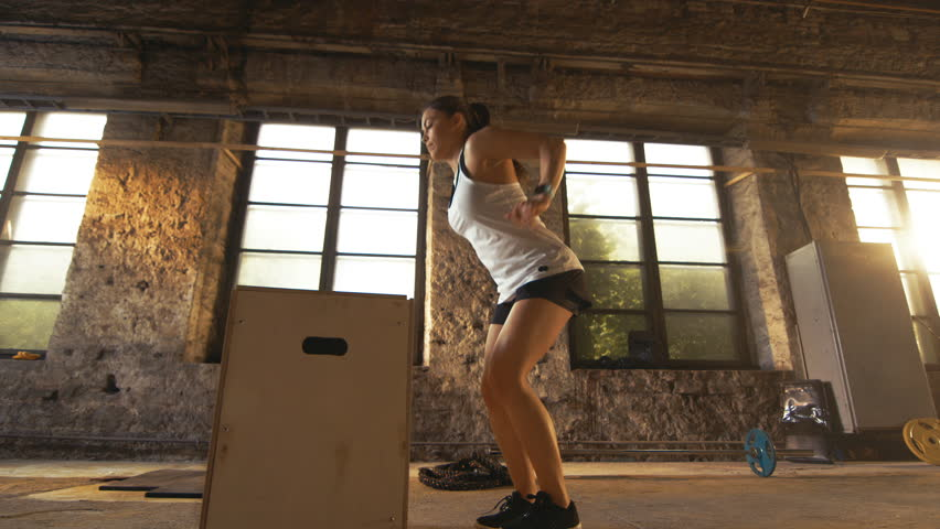 Fit Athletic Woman Does Box Jumps in the Deserted Factory Gym. Intense Exercise is Part of Her Daily Cross Fitness Training Program. Shot on RED EPIC-W 8K Helium Cinema Camera.