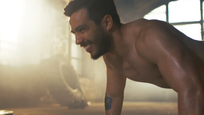 Muscular Shirtless Man Covered in Sweat Does Push-ups in a Deserted Factory Remodeled into Gym. Part of His Cross Fitness Workout/ High-Intensity Interval Training