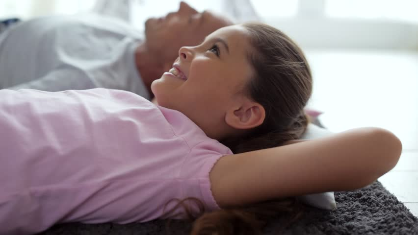 Cheerful little girl lying on the floor with her father | Shutterstock HD Video #29882743