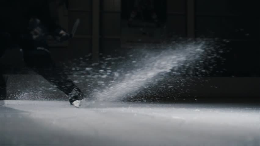 Hockey player make ice sparkles on high speed braking. Motion blur. Legs view only, hockey stick in hands, canadian tricks, stop abrupt deceleration