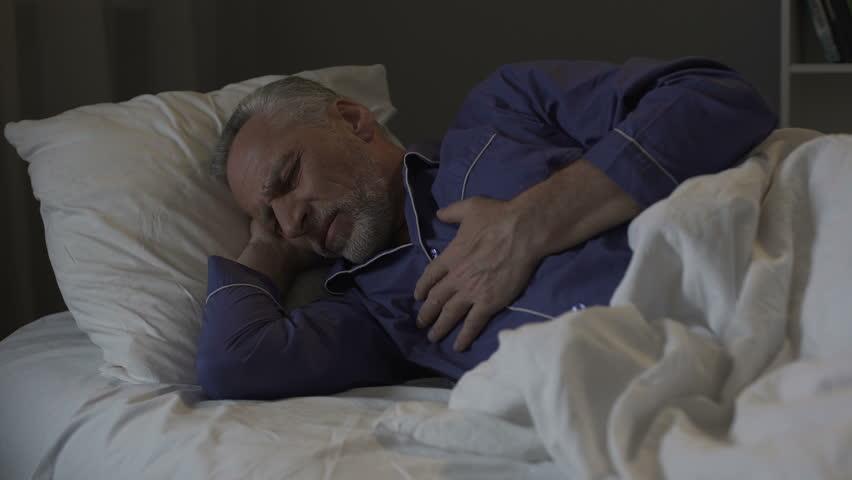 Senior man having heart attack, suffering sharp chest pain while sleeping