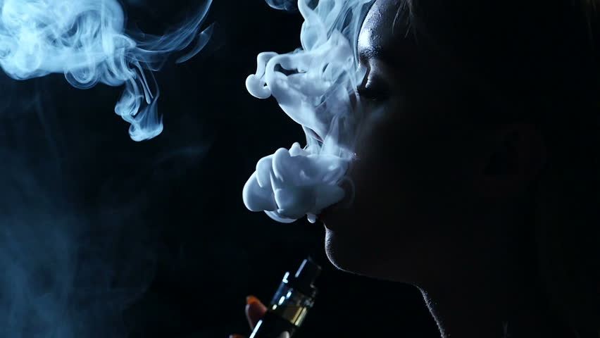 Girl smokes an electronic cigarette. Black background. Close up. Silhouette. Slow motion