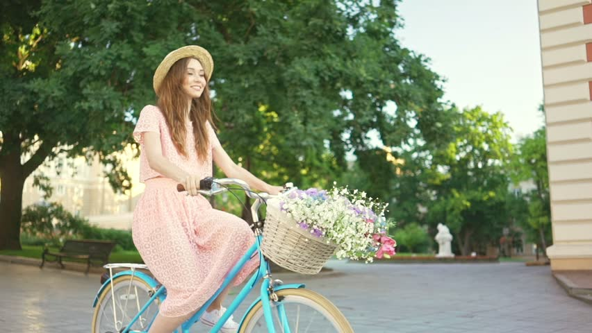 Young laughing lady in hat and pink dress riding a bicycle with flowers and smiling in the morning