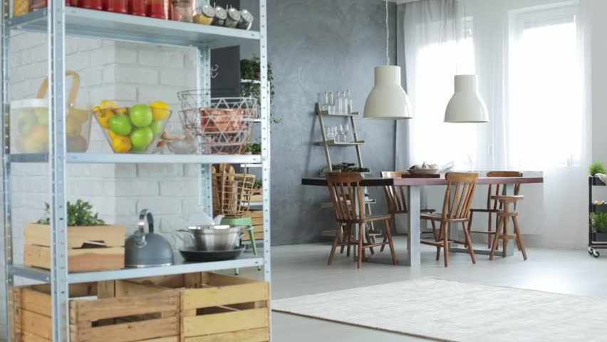 Kettle and fruits on metal shelf in dining room with white designed lamps above communal table