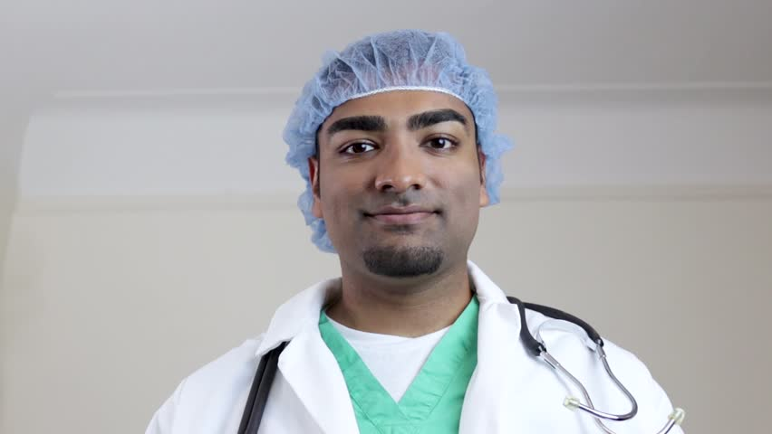 Surgeon looking forward placing mask on face