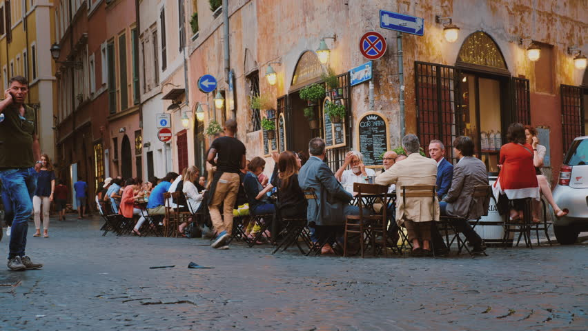 Rome, Italy - June, 2017: Street life in the center of Rome. Visitors eat in a cafe, walk along the street and take pictures of tourists