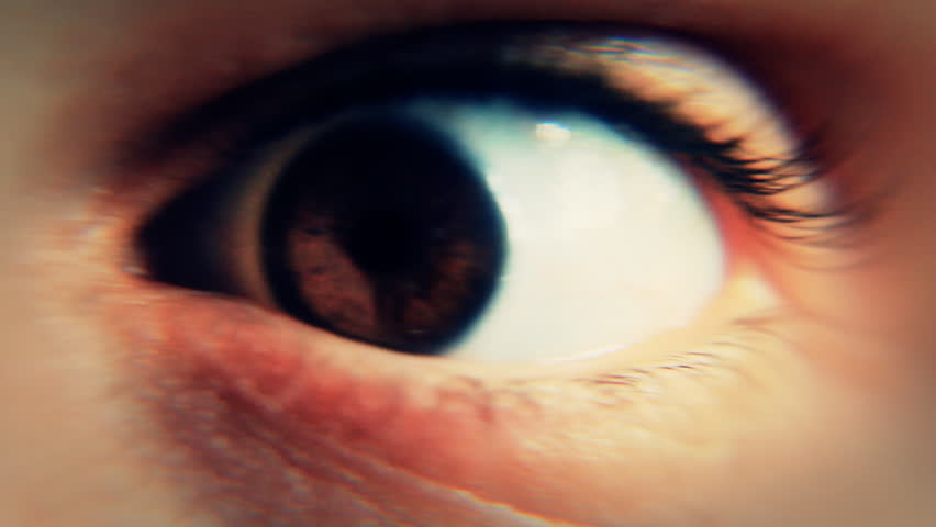 Close-up of the eye of a man awakened abruptly and having a frightened reaction, looking around.