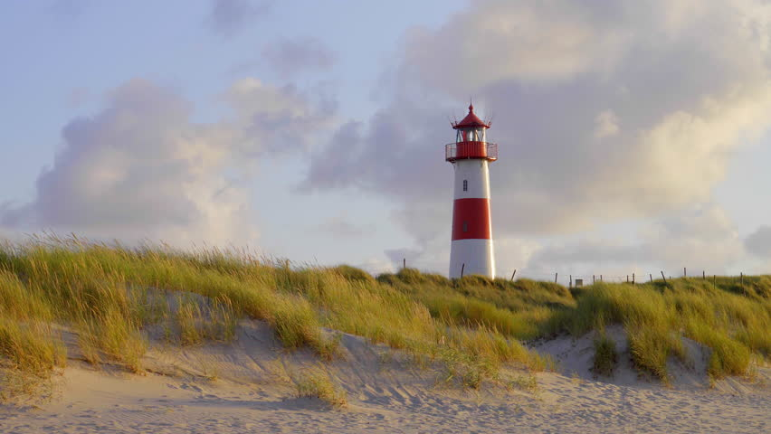 Red an white lighthouse on top of an s sand dunes in beautiful sunset light on the german holiday island sylt