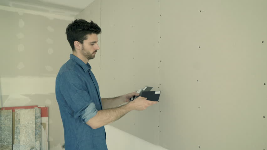 Young man checking, trying paint from palette on wall for his new home  #29965321