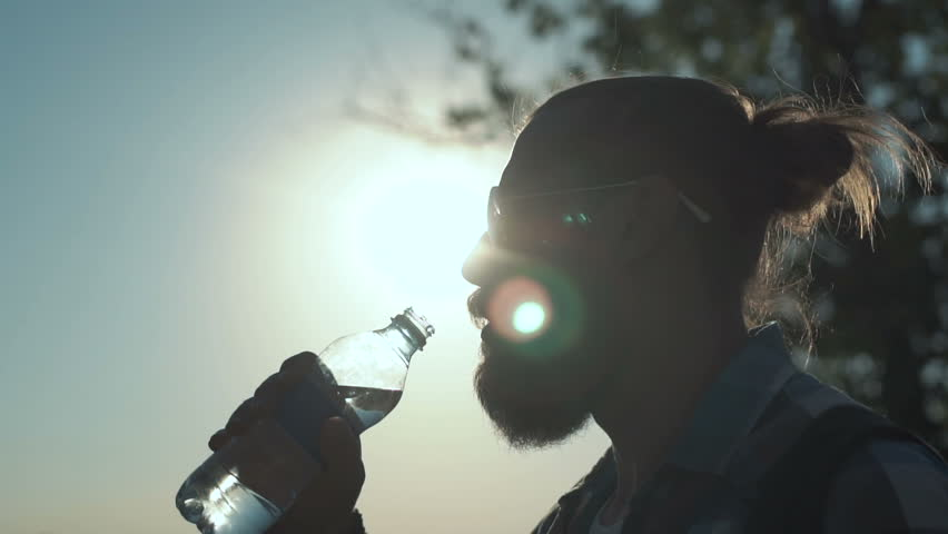Slow motion shot of side view of stylish man with ponytail drinking water from bottle on background of sunlight and nature. | Shutterstock HD Video #29966935
