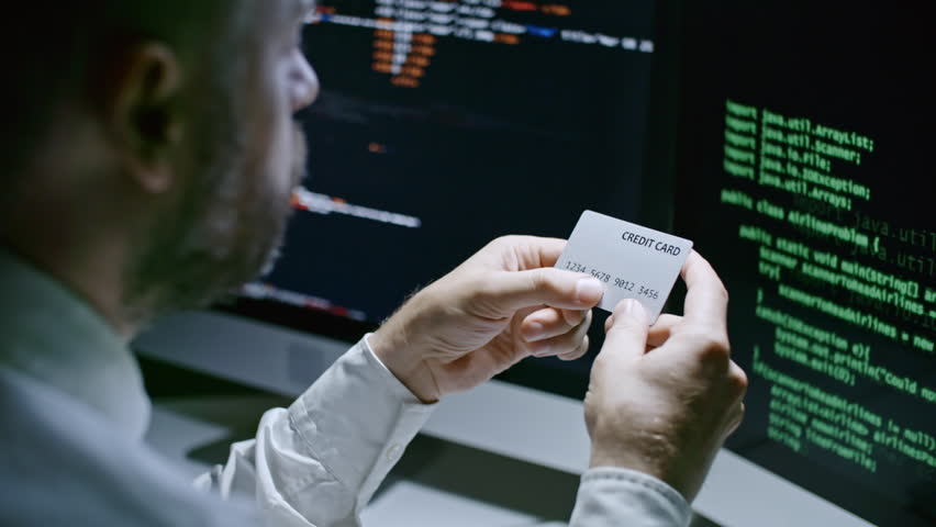 Closeup of businessman sitting at desk in front of computer screens with program codes and reading number on credit card | Shutterstock HD Video #29973892