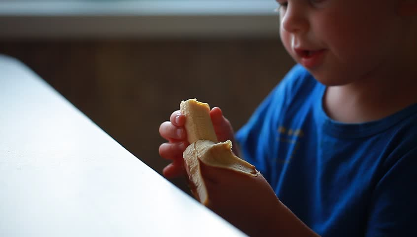 Video boy is eating a banana sitting at the table   Shutterstock HD Video #29983678
