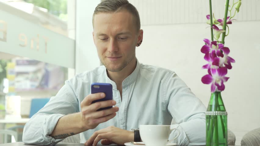 Man using app on smartphone drinking coffee, texting on mobile phone | Shutterstock HD Video #29985661