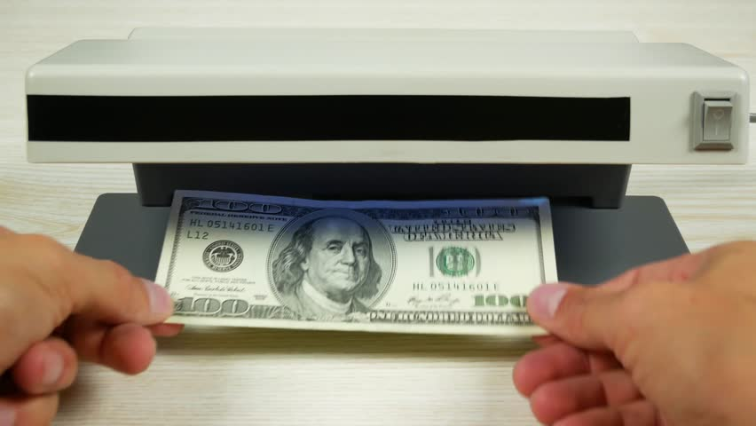 One hundred dollars in the detector look like a one-dollar bill. Detection of counterfeit money.  | Shutterstock HD Video #29995675