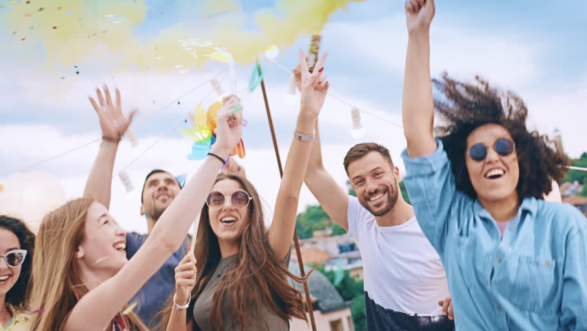 Diverse Young Party People On Rooftop Lifting Up Sparkler Fire In The Air In Colorful Smoke Holding Sparkler Fire In Rain Of Confetti Relaxation And Joy Friendship Concept At Sunset Shot on Red Epic W | Shutterstock HD Video #30008386