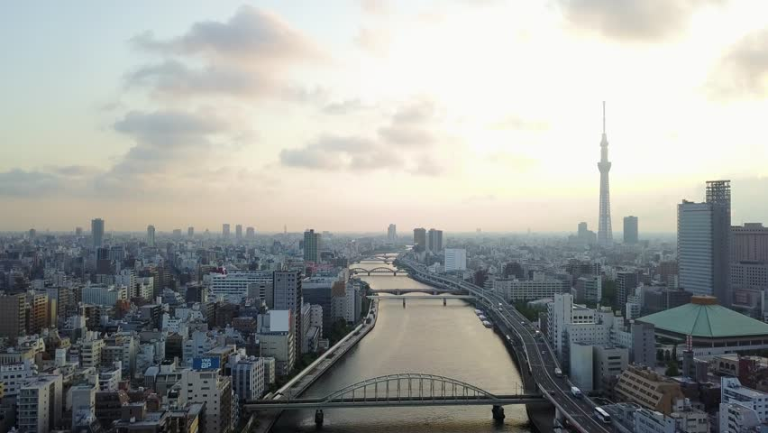 Aerial : Drone shooting of the landscape in Tokyo city Japan backward view Tokyo sky tree and the river and the bridge and roadway