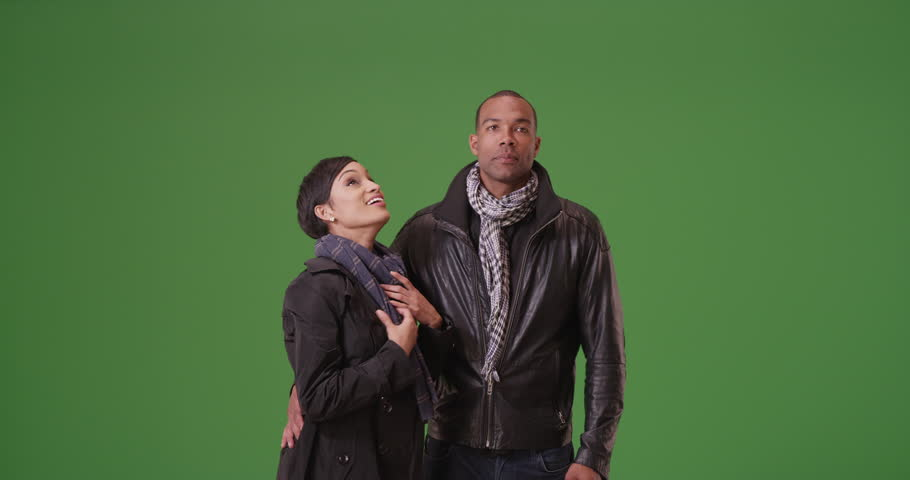 A black man and woman act playfully on green screen. On green screen to be keyed or composited.