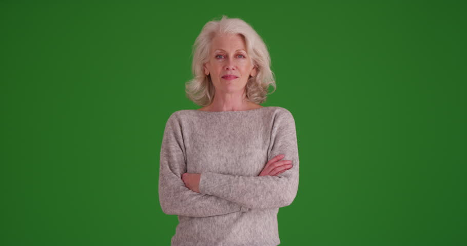 Portrait of mature woman in her 50s smiling at camera with arms crossed on greenscreen. Lovely elder woman looking at camera confidently on green screen to be keyed or composited.