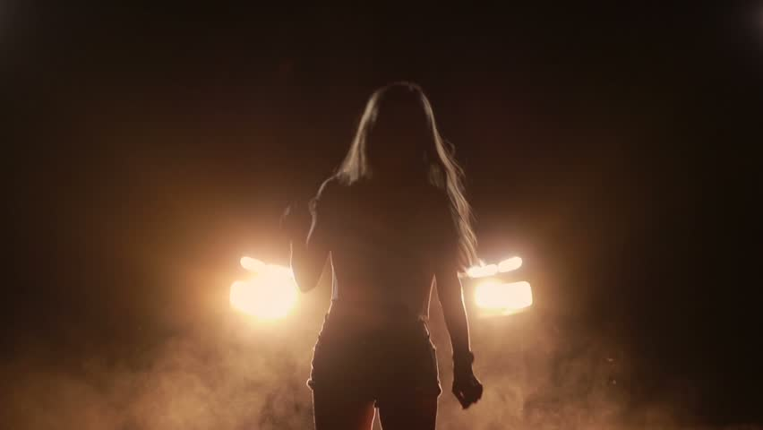 Excited girl dancing in car headlights at night