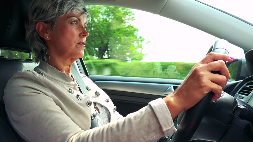 Middle aged woman drives a car in summer day  #30027451
