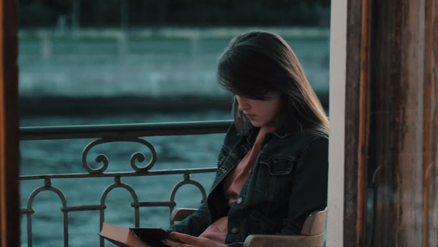 Young woman student reading literature on a summer evening on balcony   Shutterstock HD Video #30031876