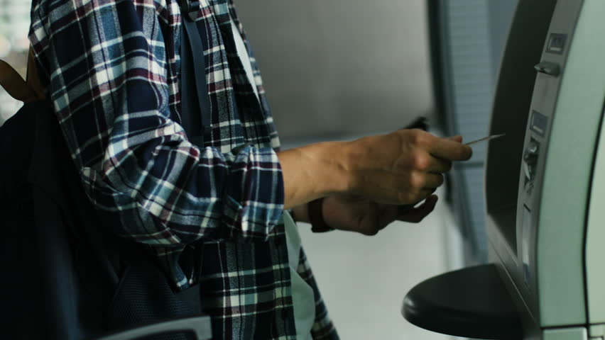 Close up shot of man hands getting money from ATM from the credit card.