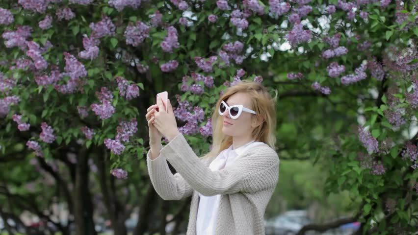 Beautiful Woman Photographed on the Phone on the Background of a Flowering Tree | Shutterstock HD Video #30051739