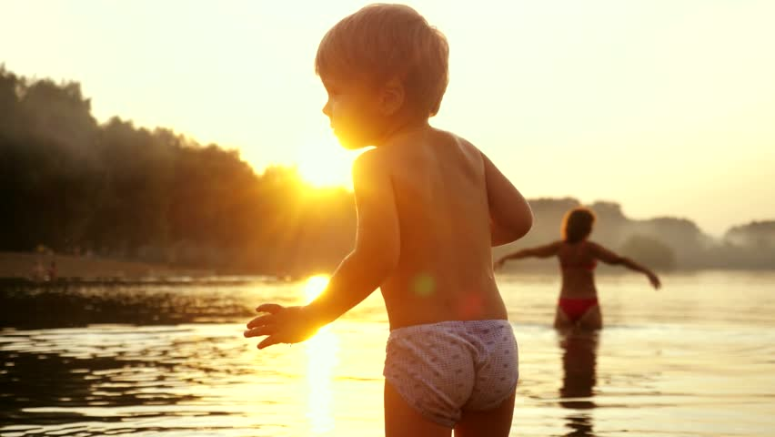 Little child stands on the beach during beautiful sunset happy vacation time in slow motion. 1920x1080 #30056299