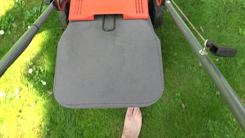 Barefeet unshod gardener man walk pushing lawn mower cutting meadow grass in yard. Handheld shot. 4K