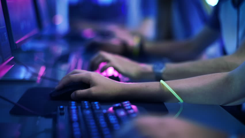Close-up On Row of Gamer's Hands on a Keyboards, Actively Pushing Buttons, Playing MMO Games Online. Background is Lit with Neon Lights. Shot on RED EPIC-W 8K Helium Cinema Camera.