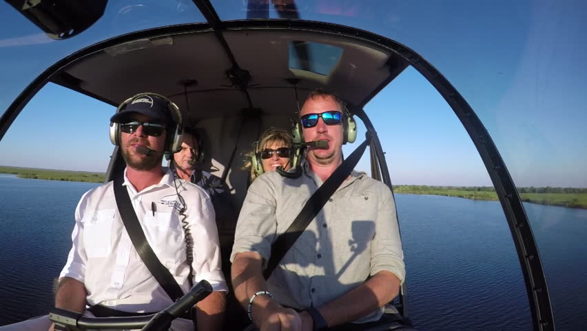POV selfie from pilot and tourists inside of a heliopter while flying over the Okavango Delta | Shutterstock HD Video #30060283