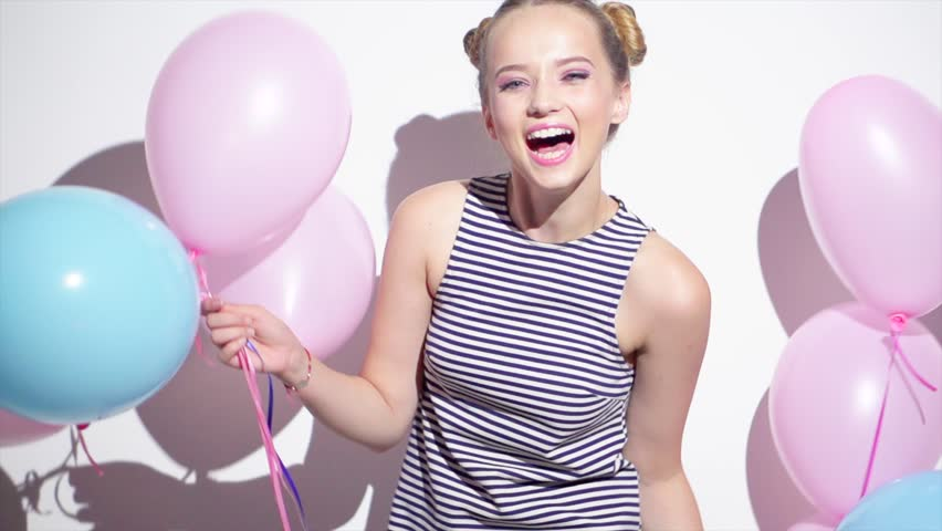Beauty girl with colorful air balloons spinning and laughing, on white background. Beautiful Happy Young woman on birthday holiday party. Joyful model having fun, celebrating. 4K slow motion video