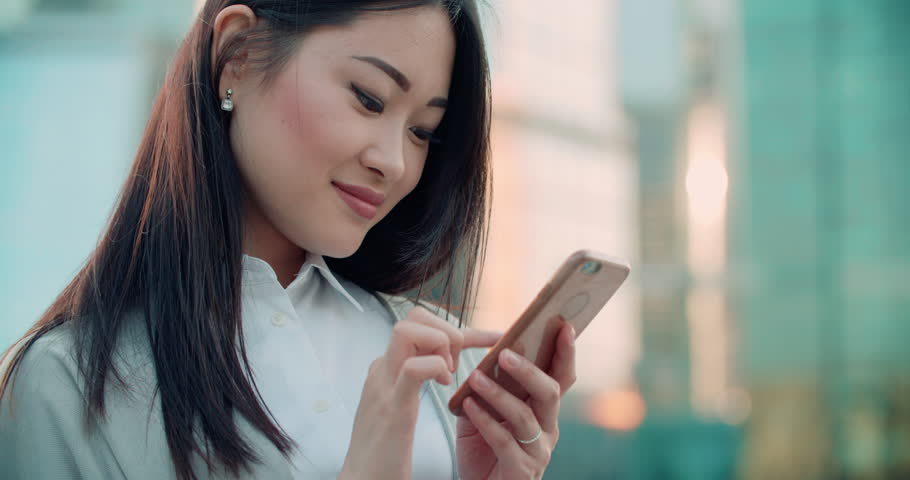 closeup of beautiful young business Asian woman with smartphone texting messenger with skyscrapers in the background Royalty-Free Stock Footage #30068623