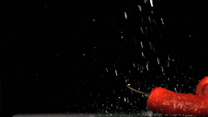 Colorful vegetables in super slow motion being soaked against a black background