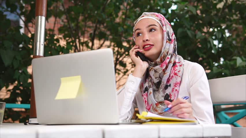 Slow motion shot of a young Muslim woman working when visiting street cafe. She making business phone calls and using laptop | Shutterstock HD Video #30071527