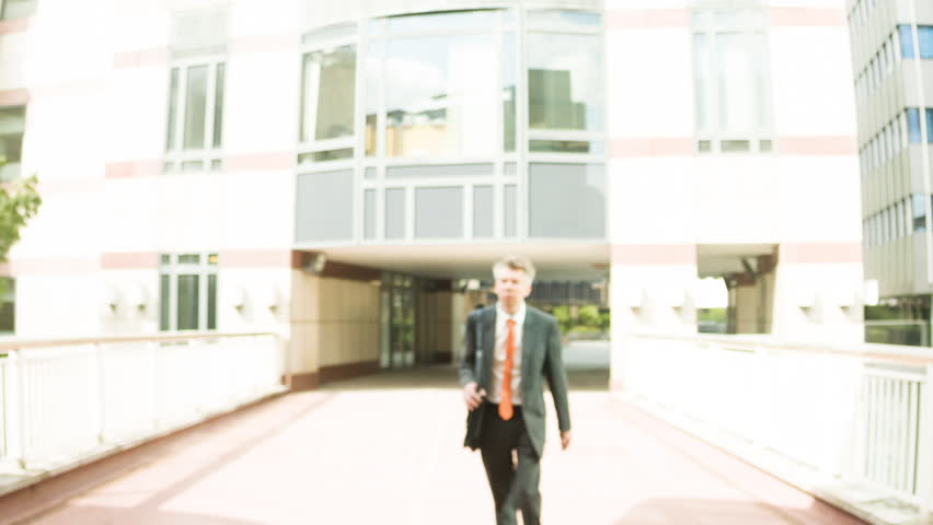 Smart Middle aged Caucasian businessman leaving the office walking past the camera | Shutterstock HD Video #30100345
