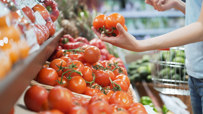 Woman's white hands take few colorful tomatoes in marketplace and hold. Closeup concept of selection and buying fruit or red vegetable. Young girl pick up some tasty freshness ingredient for cooking