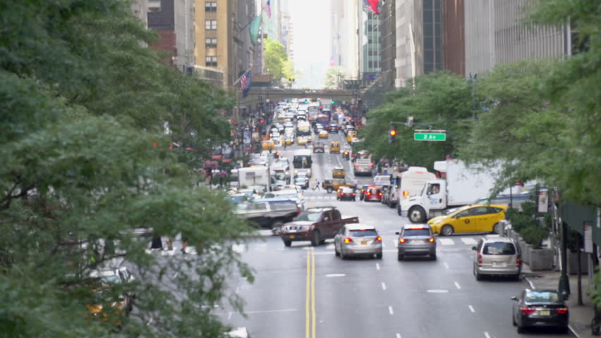 Long overhead view down 42nd street as busy traffic drives through road intersections. Day time DX exterior