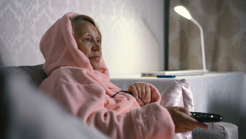 Senior woman switches the TV channels on the sofa in the home interior. Close-up | Shutterstock HD Video #30109528